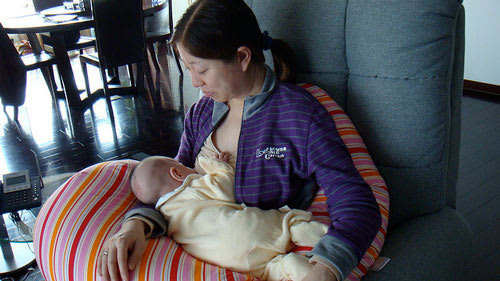 Mother breastfeeding in her living room