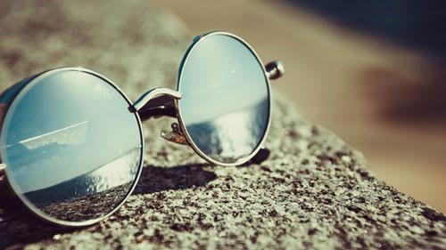 round sunglasses for skin care on concrete