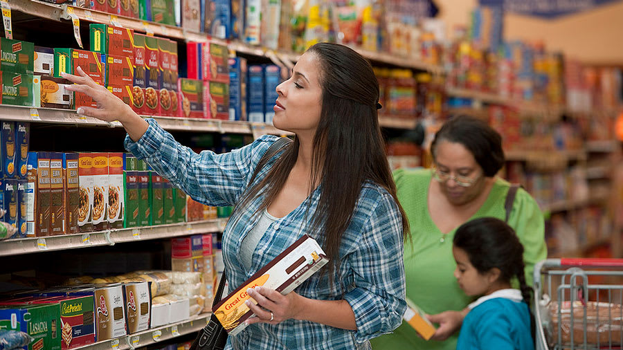 woman reading food labels in grocery aisle