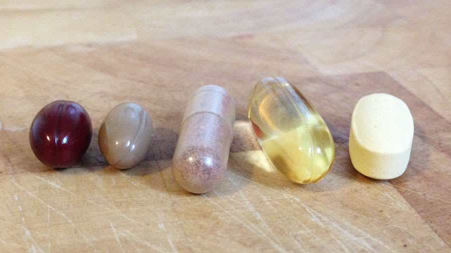 five supplement pills for skin on a table