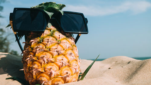 pineapple with sunglasses in sand