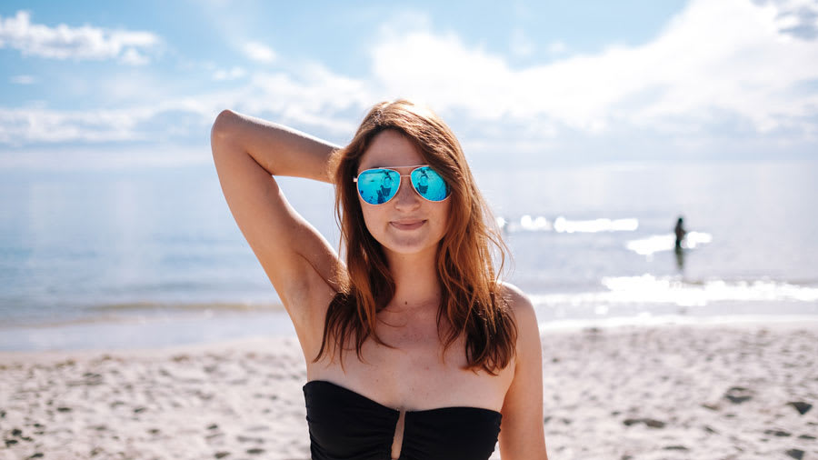 woman wearing black top and sunglasses standing on beach