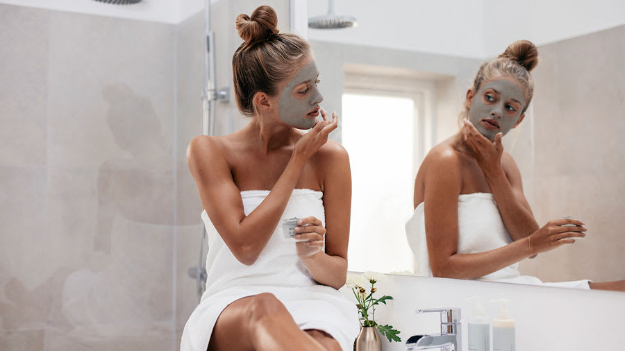 woman sitting on bathroom counter applying clay face mask in front of mirror