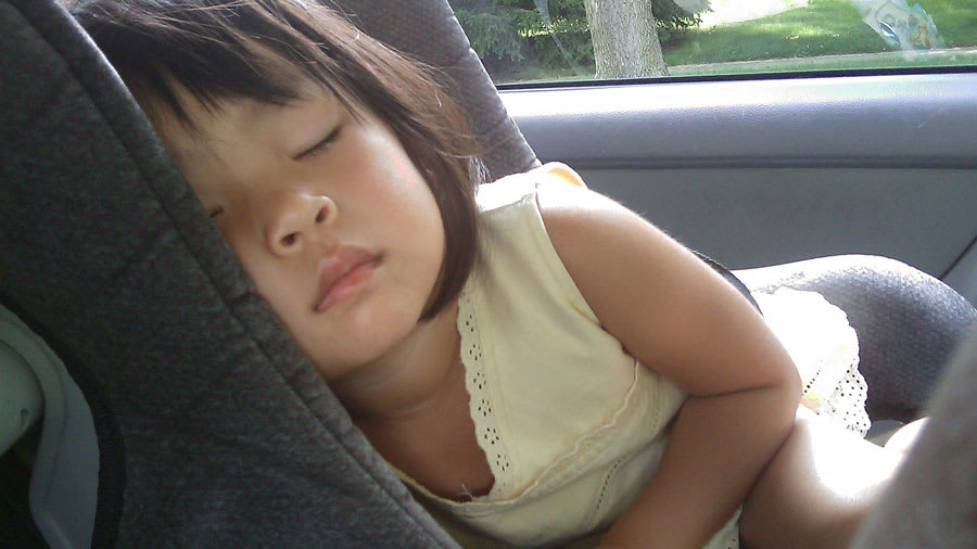 Asian female child sleeping in carseat
