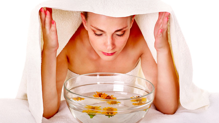 Woman getting an herbal steam facial