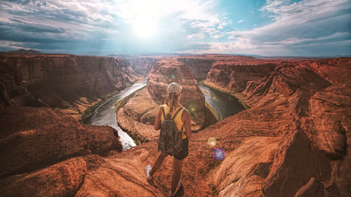 Woman looking over a large canyon and river with a beautiful view