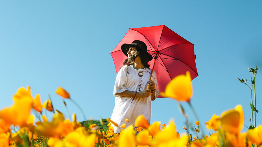 Woman holding red umbrella outside on sunny day with orange flowers on the ground