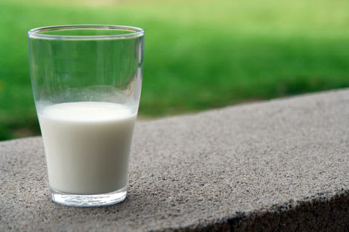 Glass of milk sitting outside on a ledge in front of grass