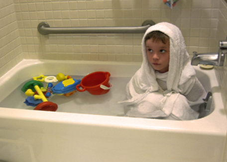 child with eczema wrapped in bathtub with towels