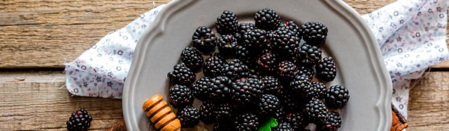 Blackberries on a plate and honey in a cup on a wooden table
