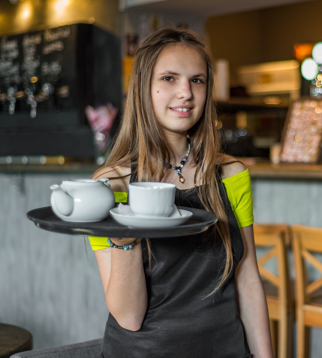A young woman working in a coffee shop thanks to support from Opportunity and Change