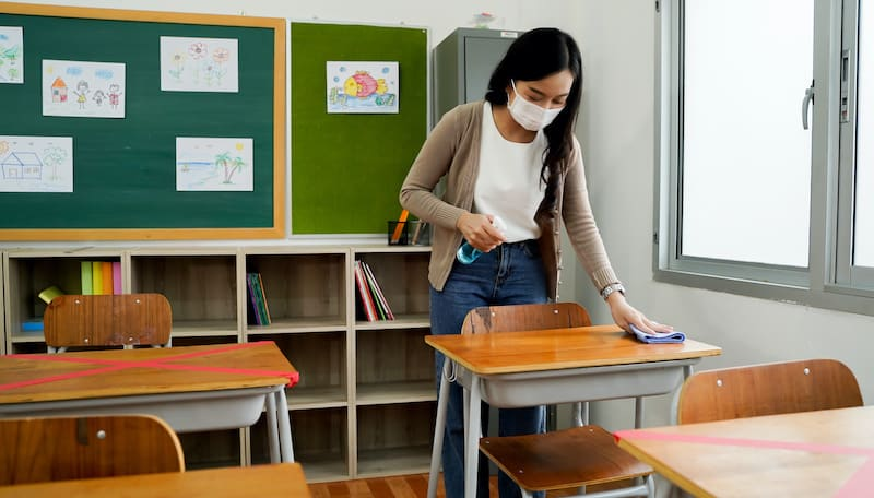 Teacher spraying a students desk with cleaner