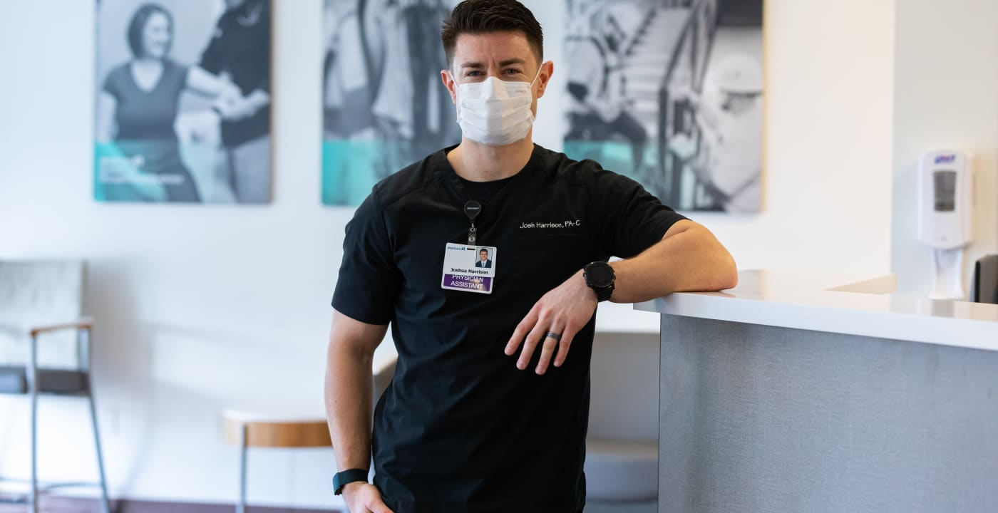 Masked medical professional leaning against the counter