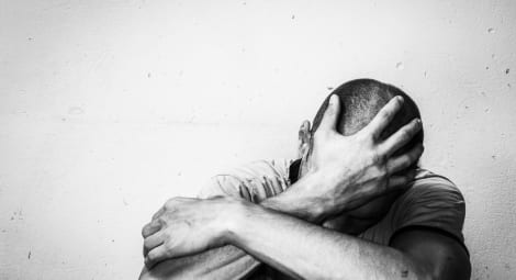 Man grabbing his head hiding his face
