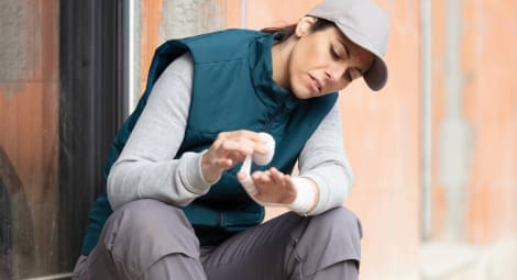 female worker bandaging her hand after incident