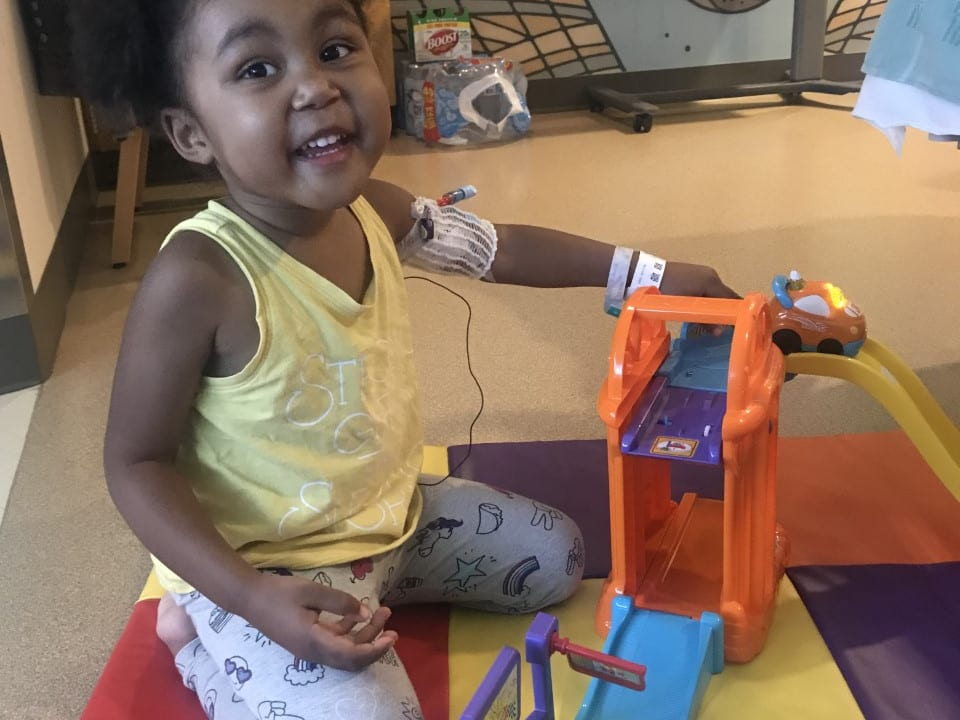Little girl playing with toys and smiling