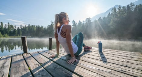 Jogging woman relaxing at lake pier
