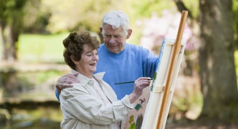 Older couple painting together outside