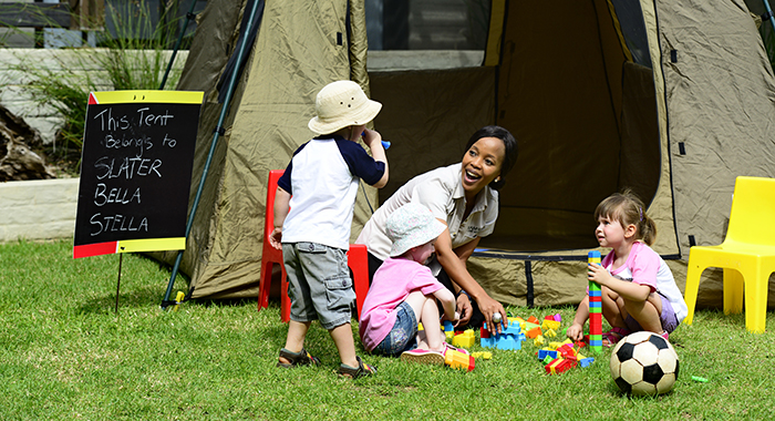 Children playing outside a tent with a supervisor