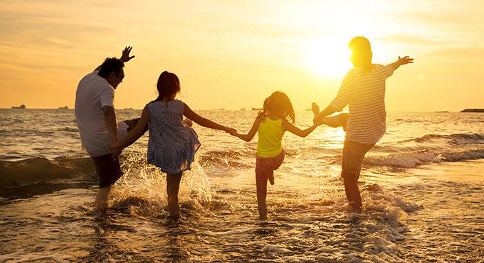 Dubai family on the beach with the sun setting