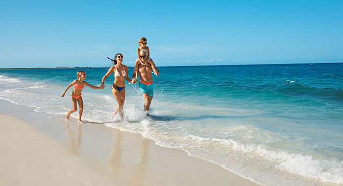 Family running along the beach and sea in swim wear