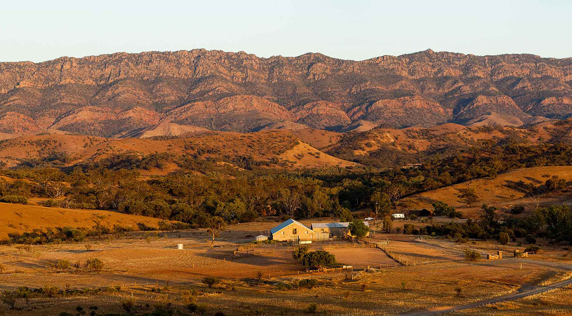 Small lodge in Australia surrounded by red and brown mountains