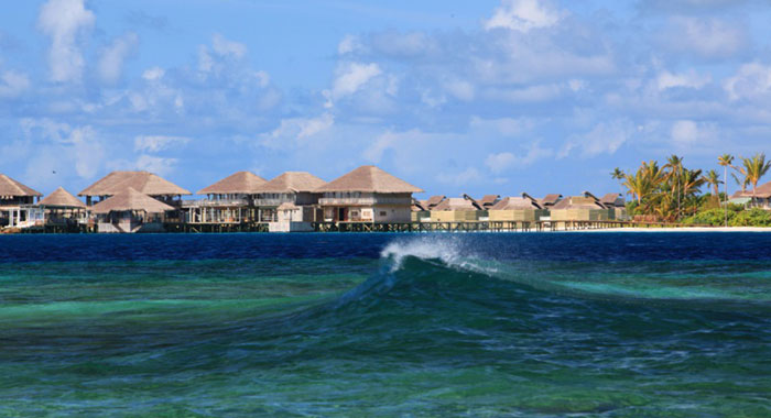 Blue ocean wave with villas on stilts in the background