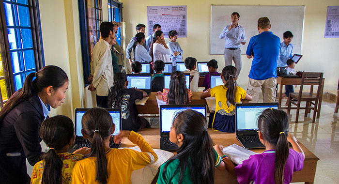 Childen and teachers in a classroom with laptops