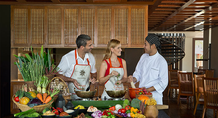 Man and woman learbing how to cook from Thai chef