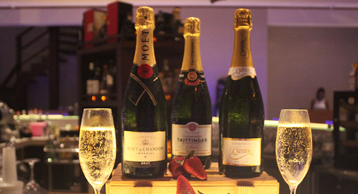 Three champagne bottles and two glasses of Champagne