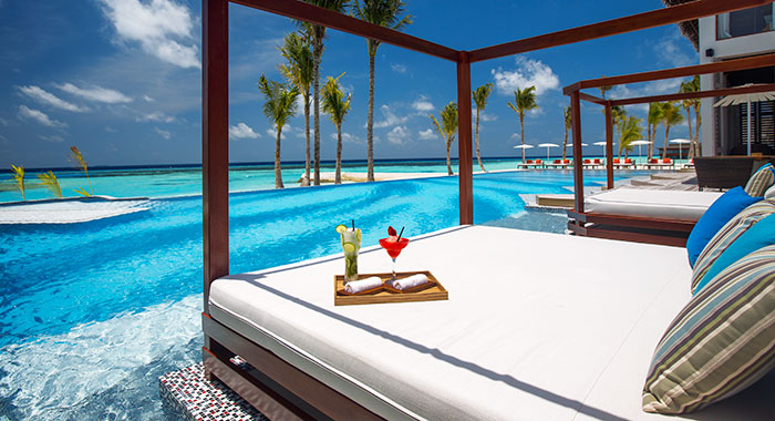 Double cabana over the swimming pool with cocktails and the blue sea in the background