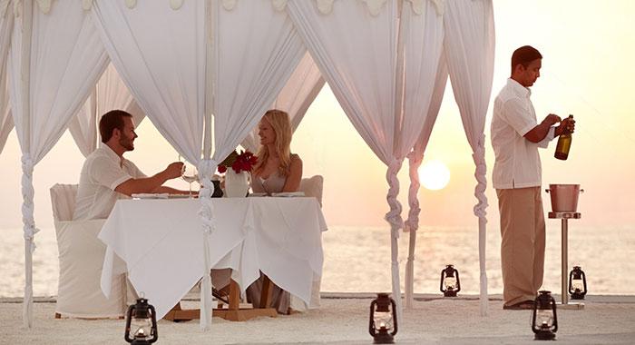 Couple dining on the beach as the sun sets