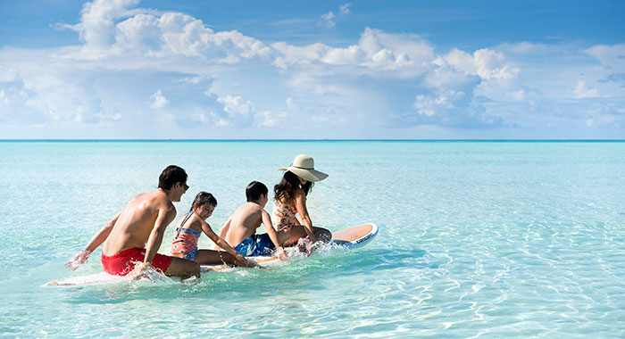A family sat on a surf board in the clear blue sea