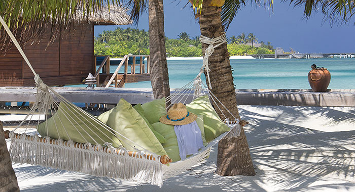 Hammock on the beach with green pillows