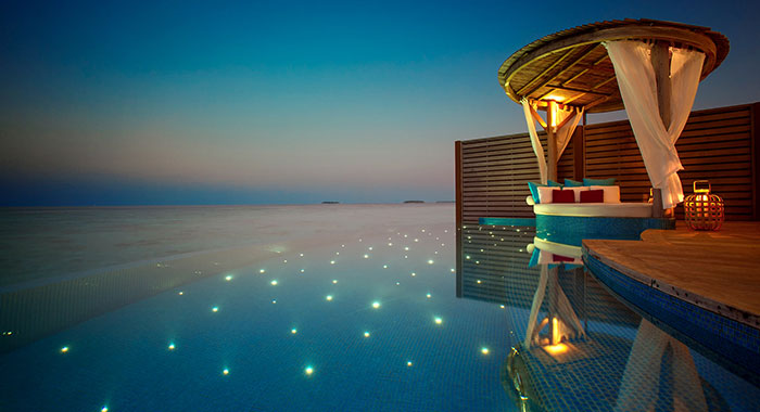 Infinity pool at night covered with twinkly lights and a cabana