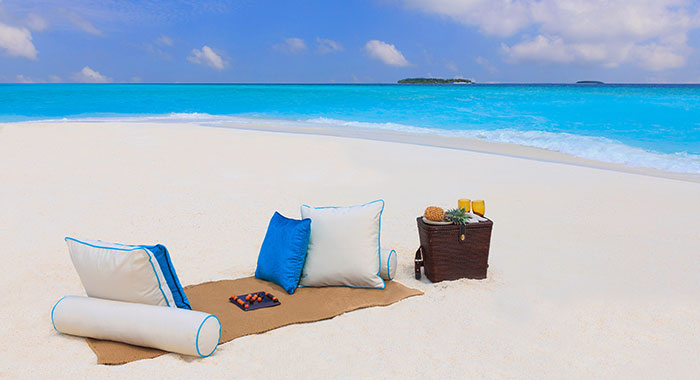 White sandy beach with pillows and hamper