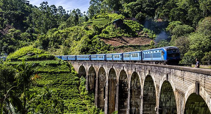 Blue train over bridge