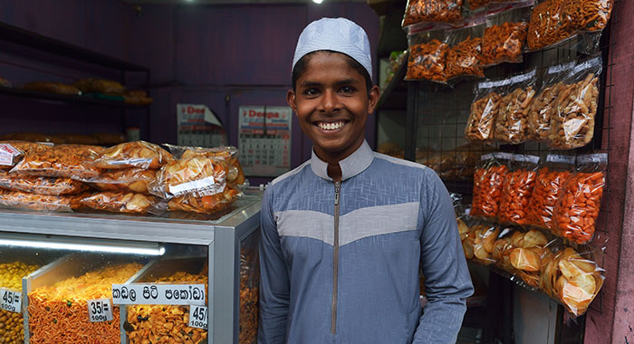 Young boy smilinh outside a stall in Sri Lanka
