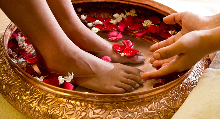 feet in a bowl with flowers in it as a spa
