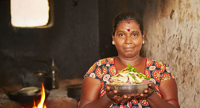 A woman holding a metal dish of food