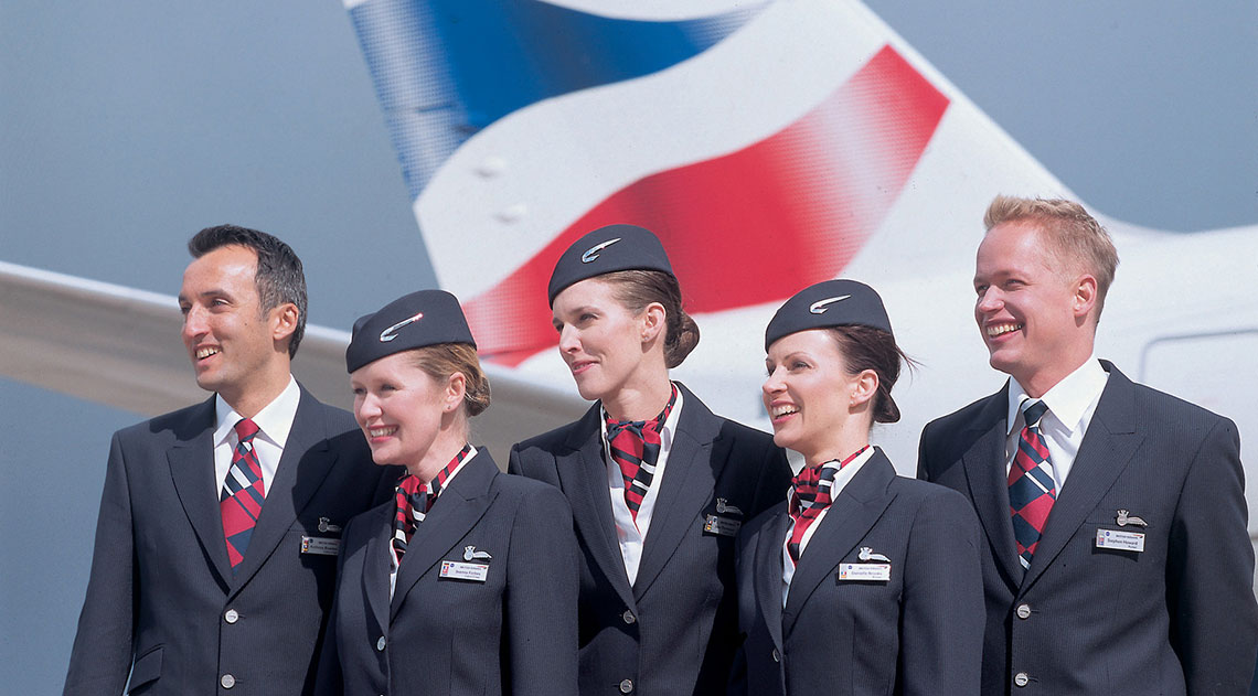 Air cabin crew stood in front of the plane