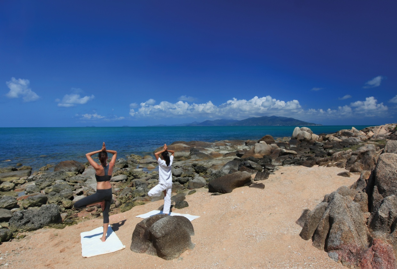 Two women practising yoga on the beach overlooking rocks