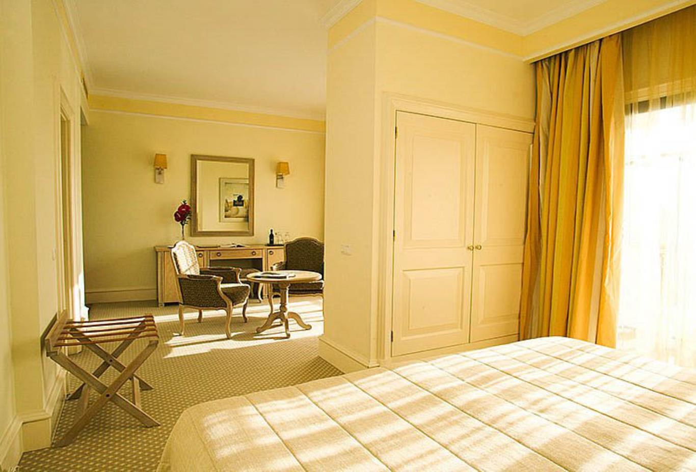 Suite with bed and sitting area - style will vary