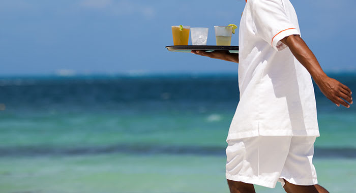 Waiter on the beach carrying orange juice
