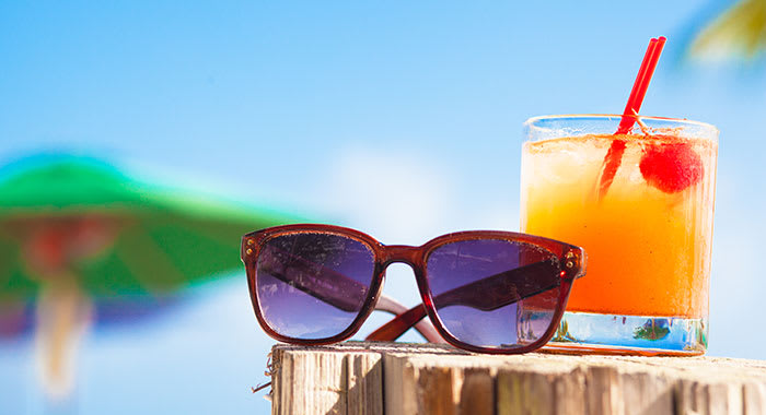Glass of orange juice and sunglasses