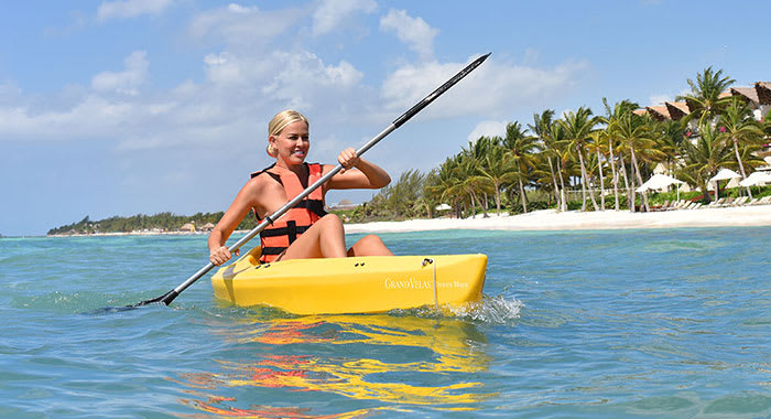 Woman with blonde hair kayaking in yellow canoe close to the beach wearing a life jacket