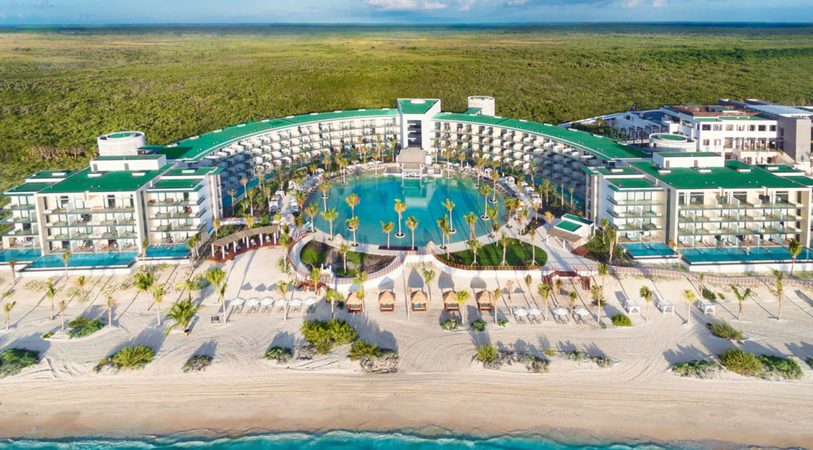 Aerial view of Haven Riviera Cancun with pool in the middle in circular shape, the beach infront of the hotel and greenery behind it