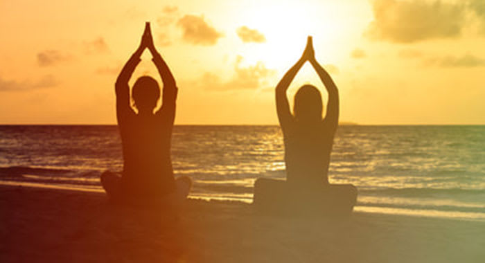 Two people practising yoga on the beach as the sun sets