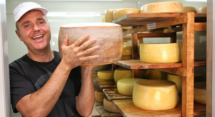 Man holding big cheese that he has produced