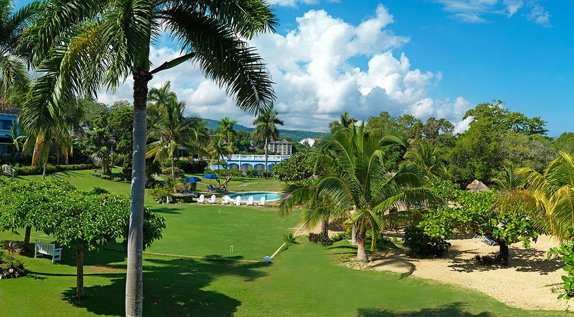 Ochios Rios resort with gardens, palm trees and a pool.